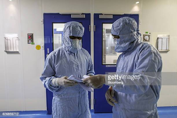 Employees in protective clothing discuss notes inside a corridor of the research and development center at the Biocon Ltd campus in Bengaluru India...