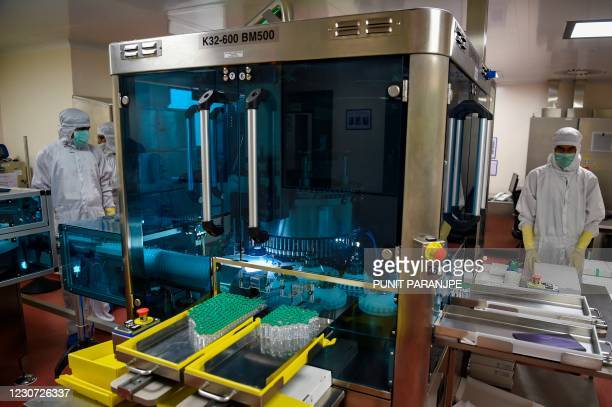 Employees in protective gear work on an assembly line for manufacturing vials of Covishield, AstraZeneca-Oxford's Covid-19 coronavirus vaccine at...