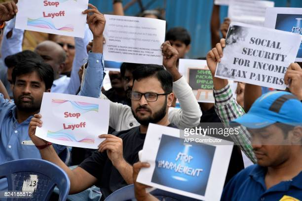 Employees in the information technology sector hold placards against layoffs and alleged unfair labour practices by Indian IT companies during a...