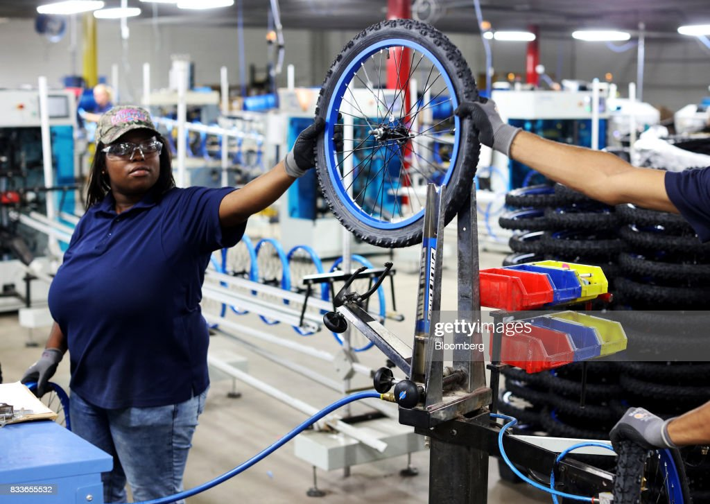 Employees inflate bicycle wheels at The Kent International Inc. Bicycle Corporation of America brand Assembly facility in Manning, South Carolina, U.S., on Sunday, June 25, 2017. Almost all of the roughly 18 million bicycles sold each year in the U.S. come from China and Taiwan. This year, about 130 workers at the Bicycle Corporation of America's new factory will assemble 350,000 bikes in the U.S. Photographer: Travis Dove/Bloomberg via Getty Images