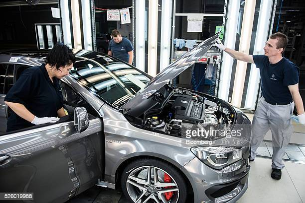 Employees inspect a CLA-class AMG automobile on the production line at the Mercedes-Benz AG automobile plant, operated by Daimler AG, in Kecskemet,...