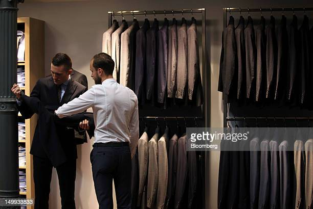 Employees inspect a suit for sale at the Gieves Hawkes store owned by Trinity Ltd on Saville Row in London UK on Tuesday Aug 7 2012 UK retail sales...