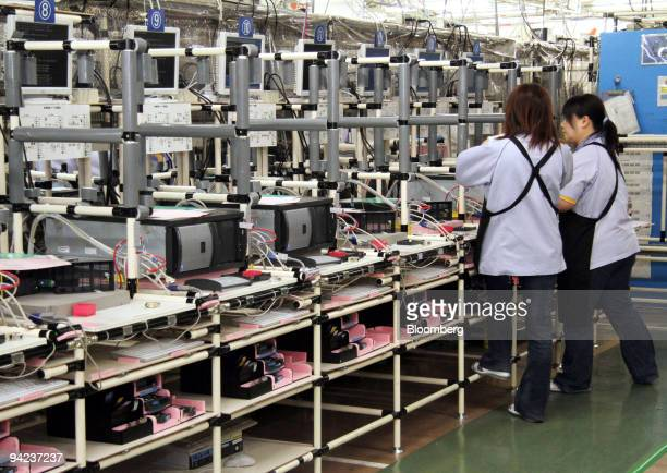 Employees inspect Fujitsu Ltd computer servers at the Fujitsu Isotec Ltd plant in Fukushima Prefecture Japan on Wednesday Dec 9 2009 Orders for...