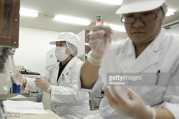 Employees inspect latex condoms during a water leaking test at a Sagami Rubber Industries Co factory in Atsugi Kanagawa Prefecture Japan on Thursday...
