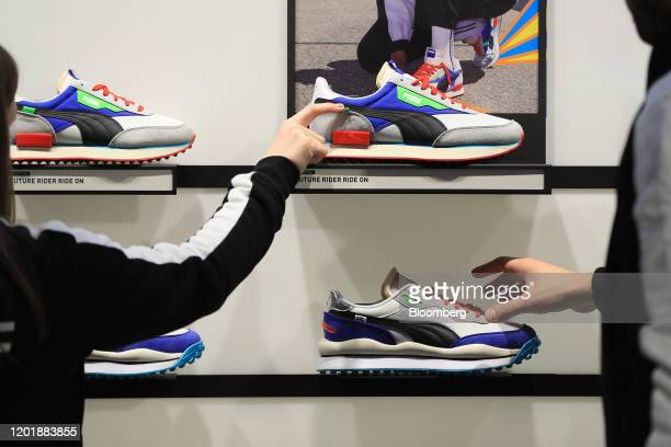 Employees inspect Puma Future Ride On running shoes inside the Puma SE concept store in Herzogenaurach, Germany, on Wednesday, Feb. 19, 2020. Puma...