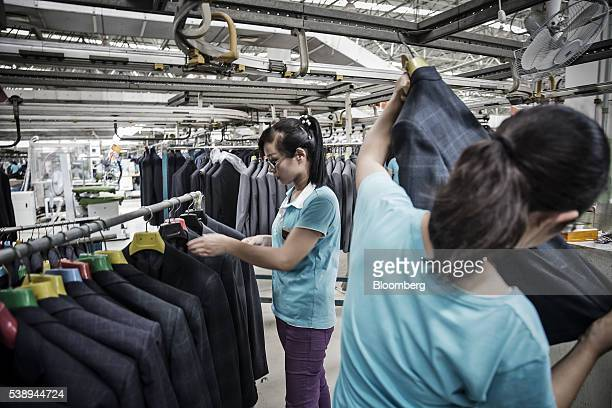 Employees inspect suit jackets at a factory operated by the Shandong Ruyi Technology Group in Jining China on Monday May 30 2016 Shandong got a boost...