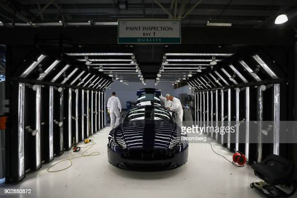 Employees inspect the bodywork of an Aston Martin DB11 luxury automobile at Aston Martin Lagonda Ltd's manufacturing and assembly plant in Gaydon UK...