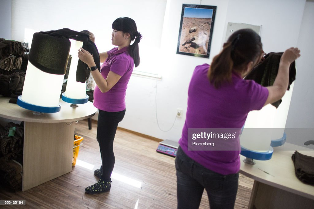 Employees inspect the quality of cashmere clothing at a Bodios Co. garment factory in Ulaanbaatar, Mongolia, on Wednesday, March 15, 2017. Mongolia's gross domestic product is expected to expand eight percent by 2019, and then grown at around five to six percent after that, International Monetary Fund (IMF) Mission Chief for Mongolia, Koshy Mathai, said in an interview last month with Bloomberg Mongolia TV. Photographer: Taylor Weidman/Bloomberg via Getty Images