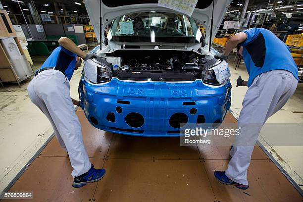 Employees install a bumper onto a Kia Motors Corp Soul vehicle on the production line at the company's plant in Gwangju South Korea on Friday July 8...