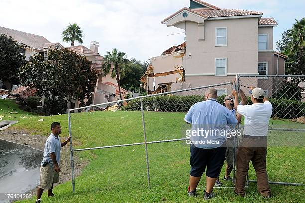 Employees install a fence around a building that is partially collapsed over a sinkhole at Summer Bay Resort near Disney World on August 12 2013 in...