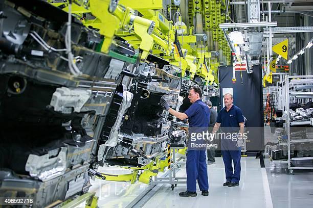 Employees install a fuel tank to a MercedesBenz SClass automobile at Daimler AG's MercedesBenz factory in Sindelfingen Germany on Monday Nov 23 2015...