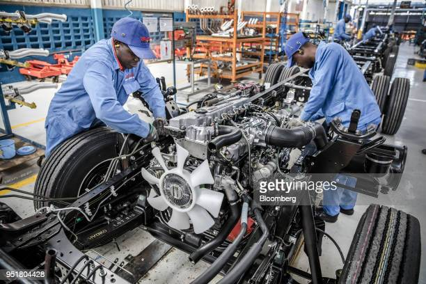 Employees install an Isuzu OHC diesel engine onto a chassis on the assembly line inside the Isuzu East Africa Ltd plant in Nairobi Kenya on Thursday...