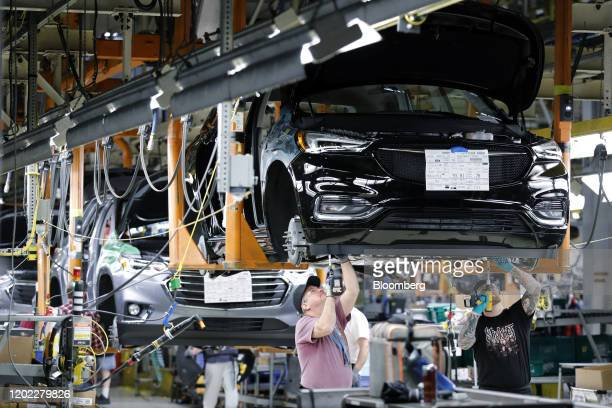 Employees install components on a General Motors Co Buick Enclave vehicle on the assembly line at the company's Lansing Delta Township Assembly Plant...