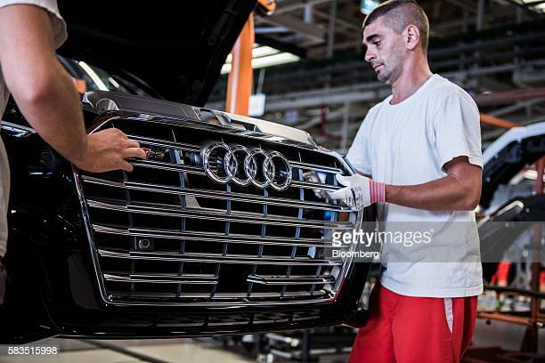 Employees install the front grille to an an Audi S3 automobile inside the Audi AG production plant in Gyor Hungary on Monday July 25 2016 The...