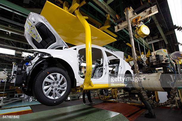 Employees install tires onto a Hyundai Motor Co. Elantra vehicle on the production line at the company's plant in Ulsan, South Korea, on Monday, July...