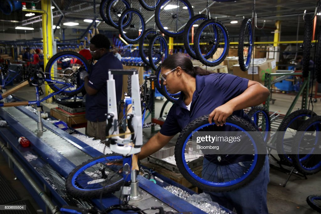 Employees install wheels on the Boys MT20 model bicycle frames at The Kent International Inc. Bicycle Corporation of America brand Assembly facility in Manning, South Carolina, U.S., on Sunday, June 25, 2017. Almost all of the roughly 18 million bicycles sold each year in the U.S. come from China and Taiwan. This year, about 130 workers at the Bicycle Corporation of America's new factory will assemble 350,000 bikes in the U.S. Photographer: Travis Dove/Bloomberg via Getty Images