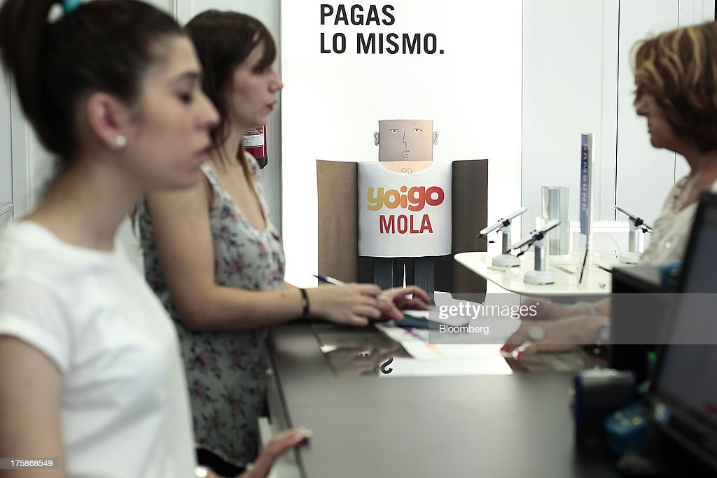 employees left talk to customers at the service desk of a yoigo