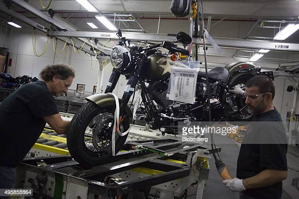 Employees lift a motorcycle up to the shipping area on the assembly line at the HarleyDavidson Inc manufacturing facility in York Pennsylvania US on...