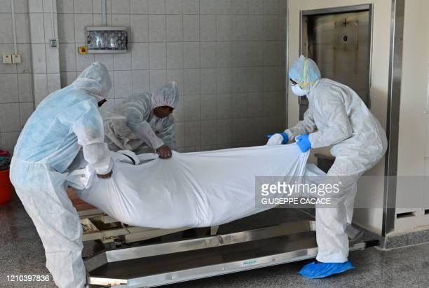 Employees lift the body of a COVID-19 victim before loading it into the furnace at the New Sonapur Hindu crematorium in the Gulf Emirate of Dubai on...