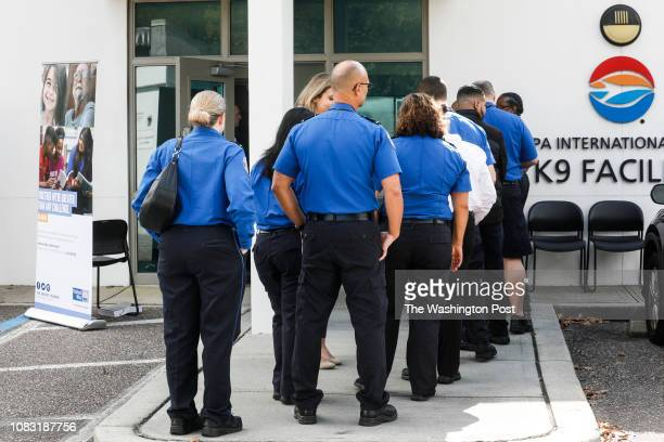 Employees line up to receive food and other resources at the pop up pantry in the police training facility at the Tampa International Airport on...