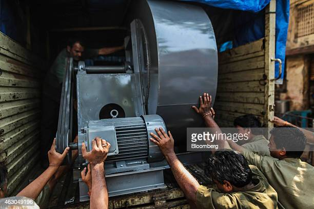 Employees load a centrifugal air blower onto a truck at an Ishwar Engineering Co factory in Mumbai Maharashtra India on Saturday Feb 7 2015 The...