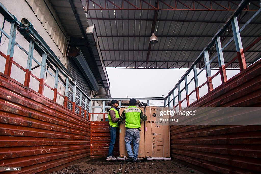Employees load an LG Electronics Inc. refrigerator onto a truck outside the warehouse at the refurbishment facility of GreenDust, a unit of Reverse Logistics Co., in New Delhi, India, on Friday, Jan. 16, 2015. Reverse Logistics, an Indian retailer of refurbished goods, is a factory outlet store in India selling goods through its GreenDust brand franchise stores and website. Photographer: Prashanth Vishwanathan/Bloomberg via Getty Images