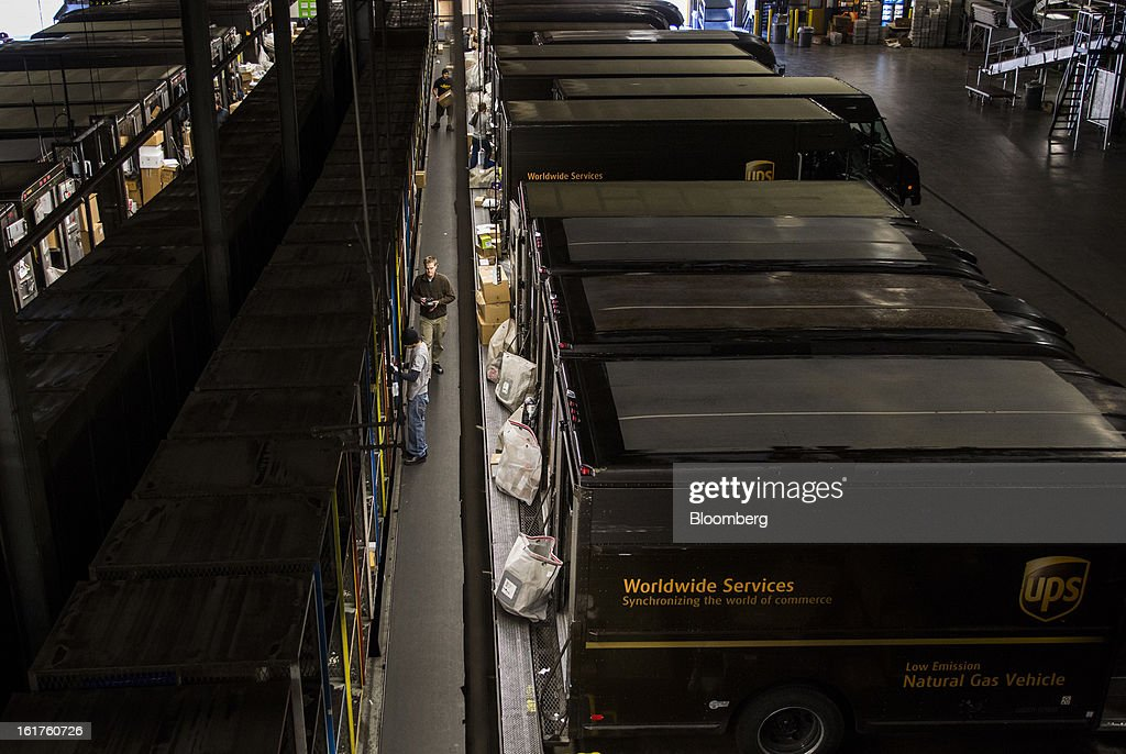 Employees load packages into delivery vehicles at the United Parcel Service (UPS) distribution center in Sacramento, California, U.S., on Thursday, Feb. 14, 2013. 100 UPS delivery all-electric vehicles, developed by Electric Vehicles International (EVI), have been deployed this week and are said to eliminate the use of 126,000 gallons of fuel per year. Photographer: Ken James/Bloomberg via Getty Images