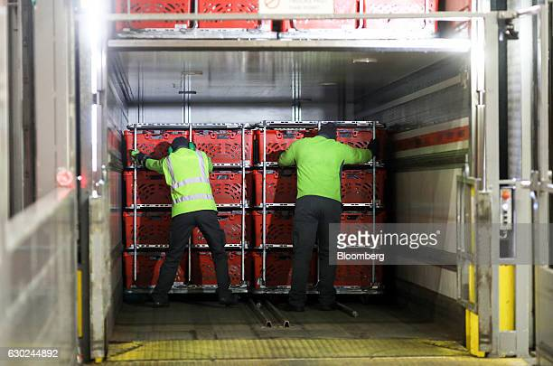 Employees load trolley loads of completed customer order crates on to a delivery vehicle at the Ocado Group Plc distribution centre in Dordon UK on...
