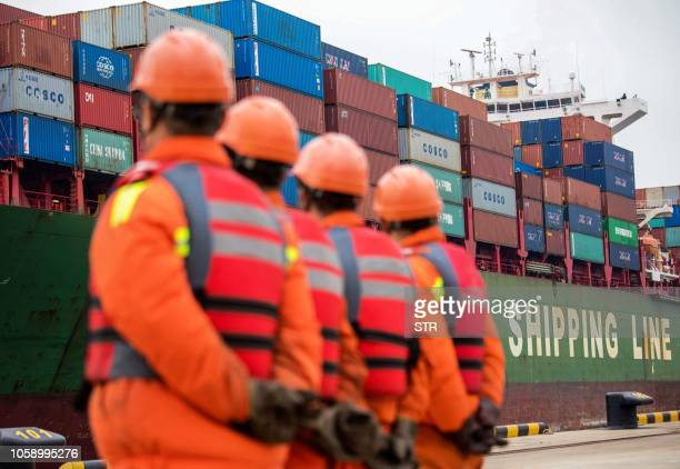 Employees look at a cargo ship at a port in Qingdao east China's Shandong province on November 8 2018 China's exports to the US and the rest of the...