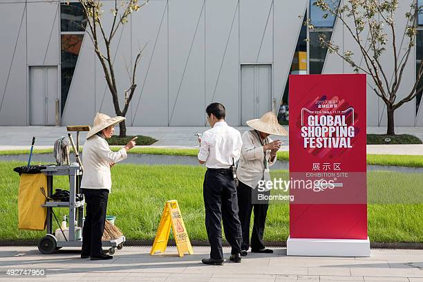 Employees look at their mobile phones while standing next to a sign promoting Alibaba Group Holding Ltd's 1111 Global Shopping Festival at the...