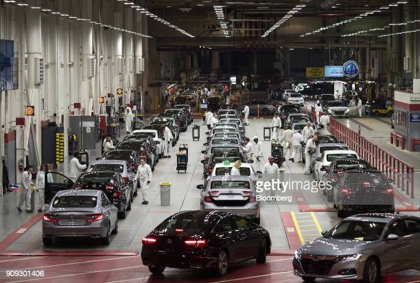 Employees look over 2018 Honda Accord vehicles on the customer preparation line at the Honda of America Manufacturing Inc Marysville Auto Plant in...