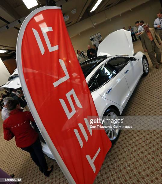 Employees looked at the Tesla S electric car as part of the 3M celebration of Earth Day with displays of other sustainable 3M products including...