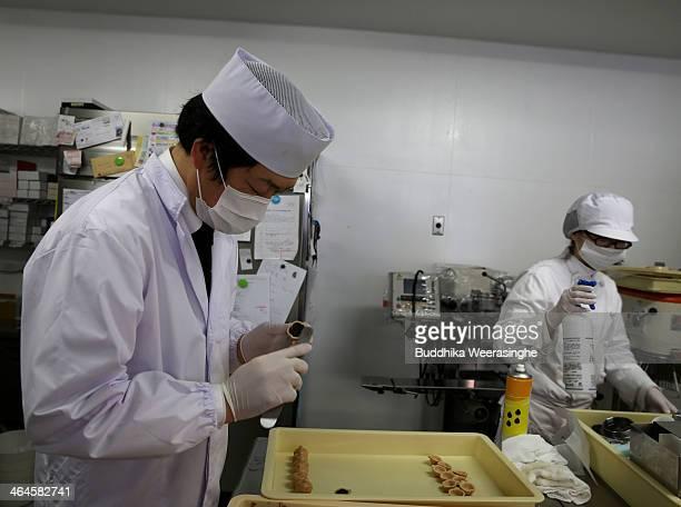 Employees make Japanese sweet named Monaka, which are made by Azuki bean at Amaneya sweet shop on January 23, 2014 in Himeji, Japan. Amaneya sweet...