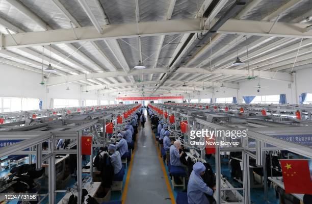 Employees make work suits at a garment factory operated by China National Nuclear Corporation on May 14 2020 in Tongxin County Ningxia Hui Autonomous...