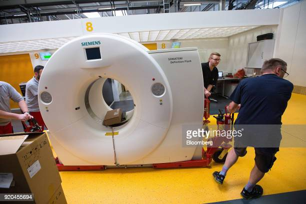 Employees maneuver a Siemens Somatom Definition Flash computerized tomography scanner machine at the Siemens AG Healthineers factory in Forchheim...