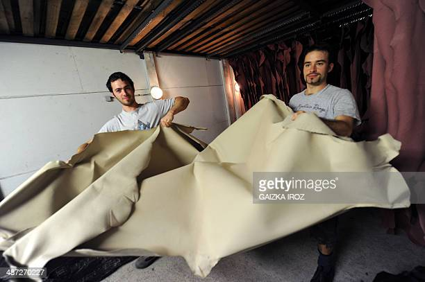 Employees manipulate skins to produce leather in the Remy Carriat tannery in Espelette southwestern France on April 10 2014 Since 1927 the tannery...