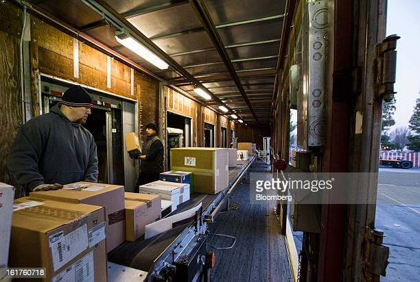 Employees Matt Webb left and Salvador Huizar unload packages at the United Parcel Service distribution center in Sacramento California US on Thursday...