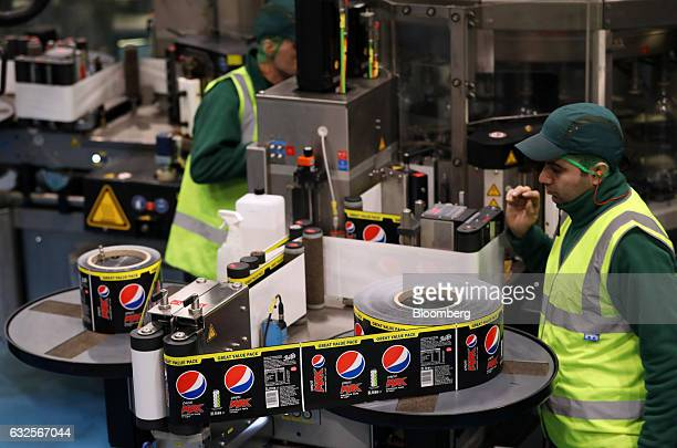 Employees monitor a Pepsi Max labelling machine on the production line at the Britvic Plc factory and warehouse in Leeds UK on Monday Jan 23 2017...