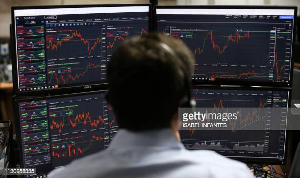 Employees monitor financial data on their computer screens as they work the brokerage ActivTrades in London on March 15 2019 The pound stabilised...