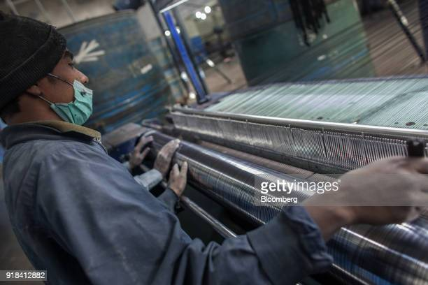 Employees monitor the tension of cotton threads on a loom in the weaving unit at the Artistic Denim Mills Ltd factory in Karachi Pakistan on Tuesday...