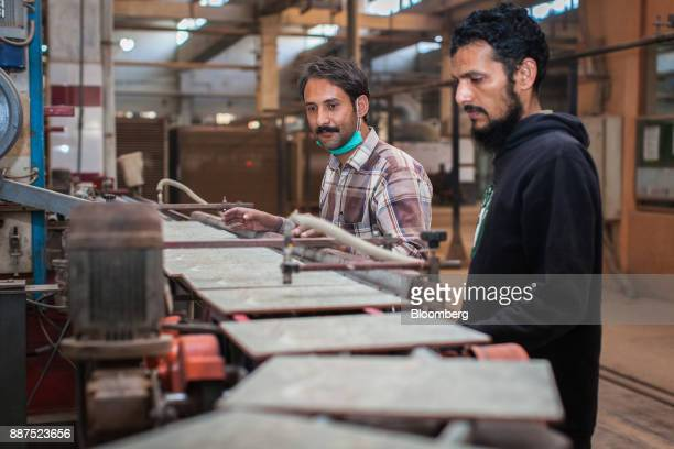 Employees monitor tiles exiting a kiln on a conveyor at the Shabbir Tiles Ceramics Ltd production facility in Karachi Pakistan on Wednesday Dec 6...