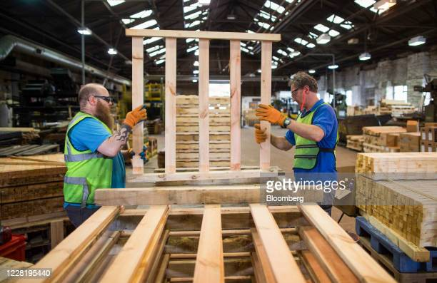 Employees move a non heat treated wooden pallet at Shaw Pallet Ltd. In Huddersfield, U.K., on Tuesday, Aug. 25, 2020. From January, wooden pallets...
