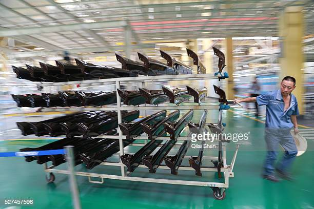 Employees move car parts through the Geely Automobile Holdings Ltd factory in Cixi Zhejiang Province China on 21 June 2012 Geely Automobile Holdings...