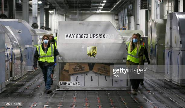 Employees move one of two shipping containers containing the first shipments of the Pfizer and BioNTech COVID-19 vaccine inside a sorting facility at...