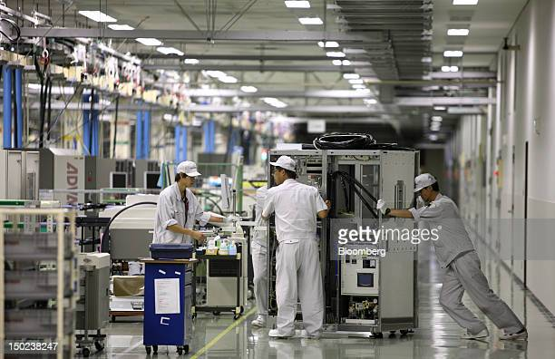 Employees move semiconductor testers on the assembly line of the Advantest Corp plant in Ora Town Gunma Prefecture Japan on Friday Aug 10 2012...