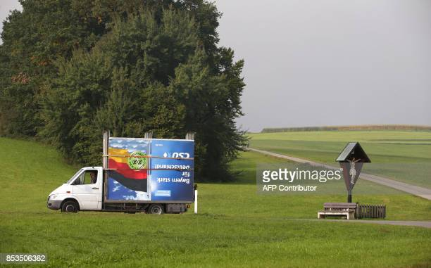 Employees of a billboard advertising company drive past a crucifix as they transport a disassembled election poster of Germany's Christian Social...
