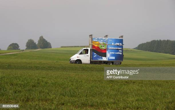 Employees of a billboard advertising company transport a disassembled election poster of Germany's Christian Social Union party into a warehouse in...