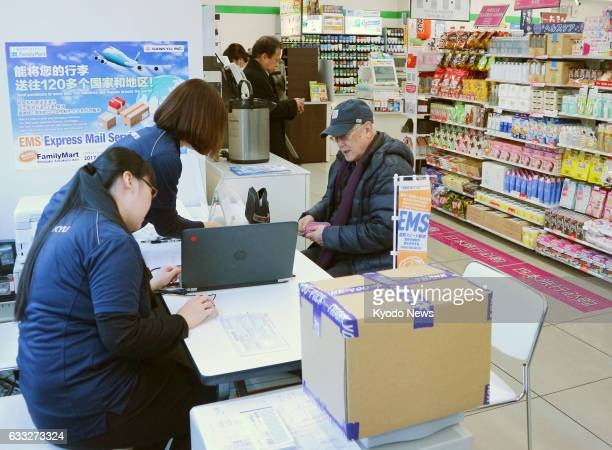 Employees of a distribution company serve at a counter for the Express Mail Service set up inside a FamilyMart convenience store in Tokyo on Jan 31...