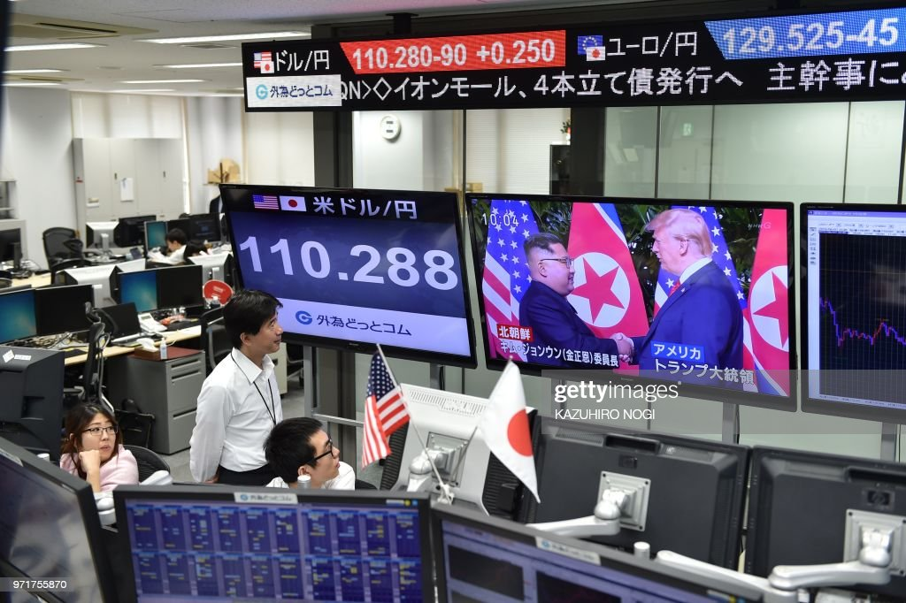 TOPSHOT - Employees of a foreign exchange trading company in Tokyo look at the screens displaying live news of meeting between North Korean leader Kim Jong Un and US President Donald Trump in Singapore, and the Japanese yen's exchange rate against the US dollar on June 12, 2018. - Donald Trump and Kim Jong Un have become on June 12 the first sitting US and North Korean leaders to meet, shake hands and negotiate to end a decades-old nuclear stand-off.
