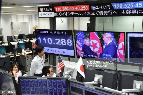 TOPSHOT Employees of a foreign exchange trading company in Tokyo look at the screens displaying live news of meeting between North Korean leader Kim...